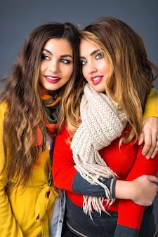 Chiuda sul ritratto di ragazze bionde e castane carine, abbracci, stile familiare sorella, stagione autunno inverno, indossando maglioni e sciarpe
