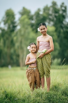 Close up, portrait of cute sister and young sister in thai traditional dress and put white flower on her ear standing in rice field,  smile , sibling love concept, copy space