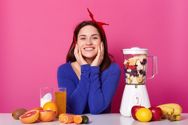 Close up portrait of cute smiling young woman with happy expression, keeps her hands on cheeks, being photographed in photo studio isolated on pink with lots of fruit and blendrer.