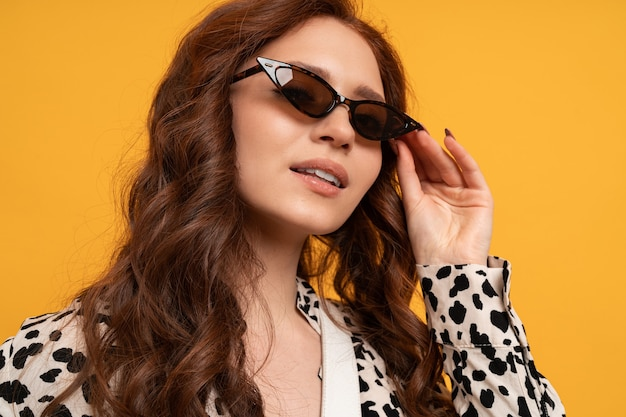 Close up portrait of cute stylish red head woman posing on yellow.