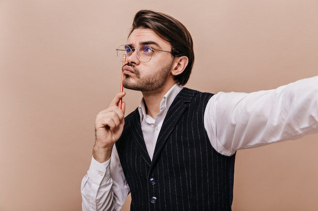 Close-up portrait of cute young gentleman in stylish glasses, white shirt and striped waistcoat, thinking with pencil and creating idea isolated over beige wall