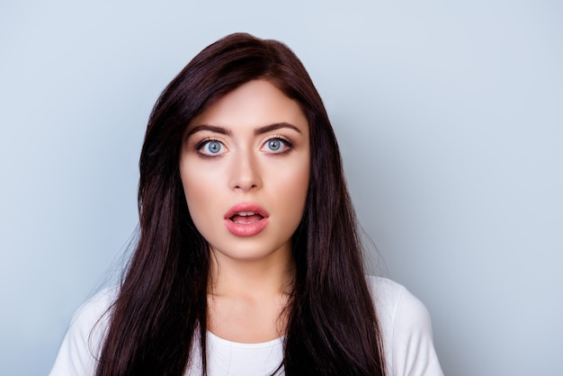 Close up portrait of cute young shocked woman with opened mouth isolated on gray space