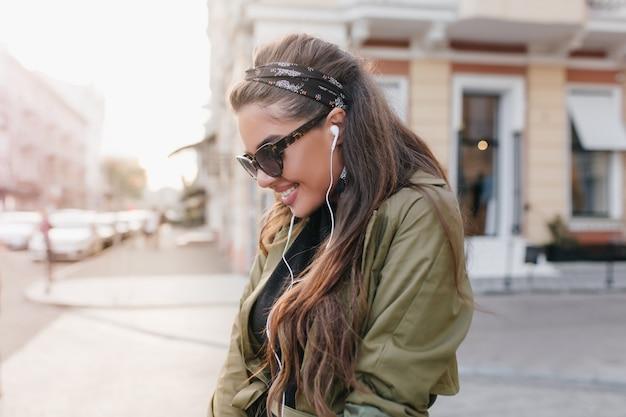 Ritratto del primo piano della signora ispanica dai capelli scuri in occhiali da sole che ride sullo sfondo urbano