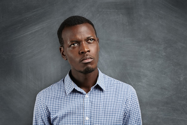 Close up portrait of dark-skinned student with pensive and concentrated expression trying to recollect something, standing at blackboard.