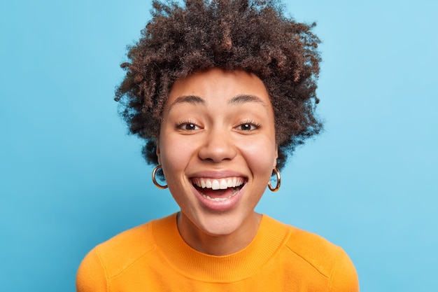 Close up portrait of dark skinned woman with natural curly hair clean healthy skin smiles broadly expresses happiness has perfect white teeth wears casual clothes isolated over blue wall.