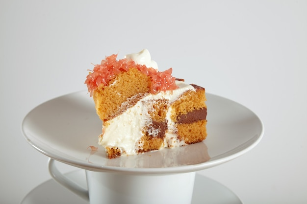 Close up portrait of a delicious sponge cake with chocolate filling, cream and grapefruit on saucers and cups