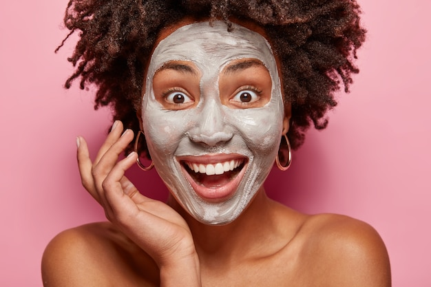 Close up portrait of delighted afro american lady has white clay mask on face, smiles broadly, surprised to have fresh skin after beauty procedures, has consultancy with beautician or cosmetologist