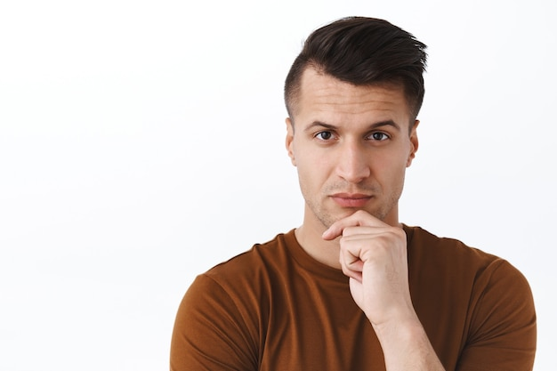Close-up portrait of determined, serious handsome adult man thinking, touch chin thoughtful, making important decision, choosing, standing white wall