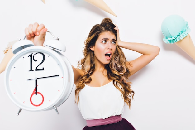 Close-up portrait of disappointed curly girl looking away, wearing trendy attire. young woman with panicking face expression holding big alarm clock on decorated wall.