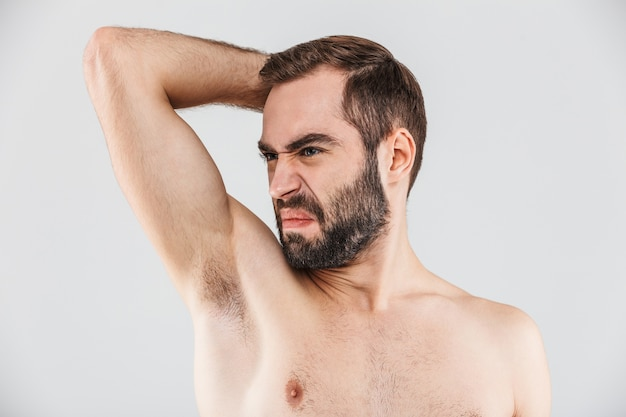 Close up portrait of a disgusted bearded man standing isolated over white, smelling his armpit