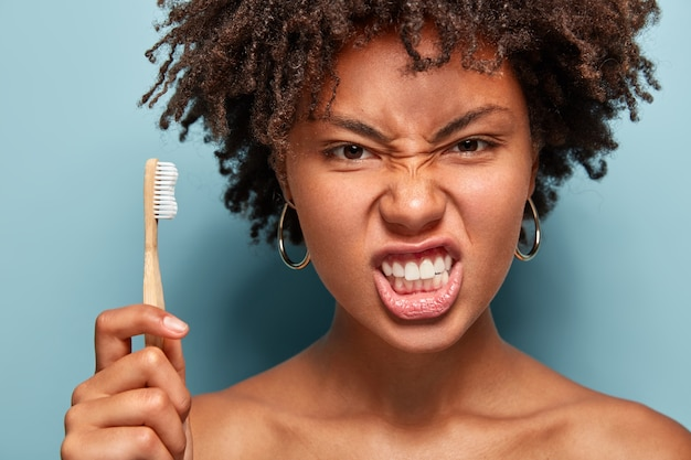 Close up portrait of displeased annoyed woman frowns face, irritated with something, holds toothbrush, cares of oral hygiene, has healthy skin, isolated over blue wall, cleans teeth indoor