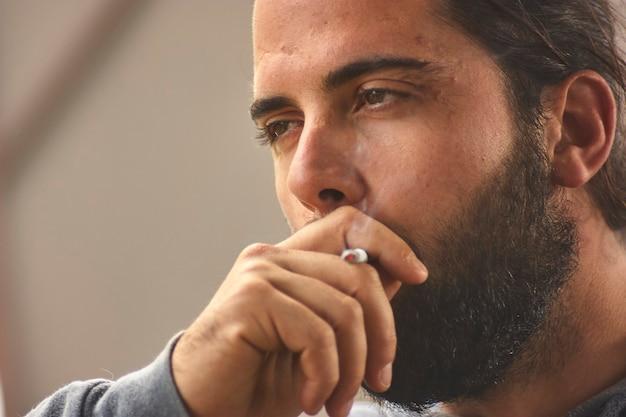 Close up portrait of dramatic man smokes