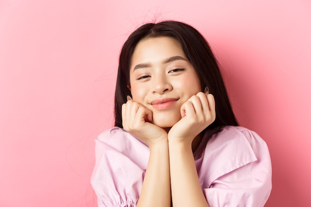 Close-up portrait of dreamy and romantic asian girl, lean face on hands and smiling, looking with admiration and happiness, standing against pink background.