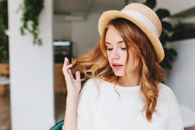 Ritratto del primo piano della giovane signora sognante con l'acconciatura riccia e la pelle pallida che indossa un elegante cappello di paglia decorato con nastro bianco