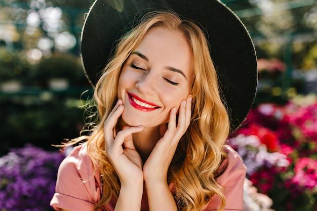 Il ritratto del primo piano della donna cieca estatica con le labbra rosse indossa il cappello nero. debinair donna bianca in posa con gli occhi chiusi vicino ai fiori.