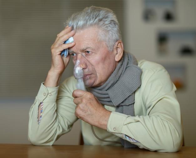 Close-up portrait of an elder man making inhalation