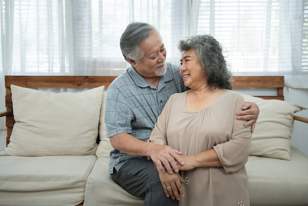 Close-up portrait of elder senior asian  attractive lovely kind sweet gentle cheerful cheery peaceful calm spouses hugging holding hands in light white interior room,portrait of retirement couple.