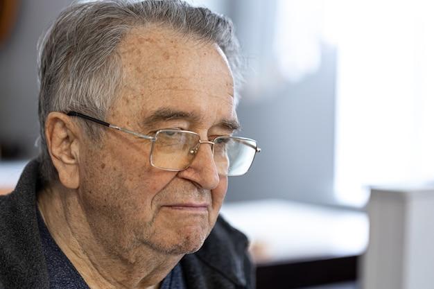 Close up portrait of an elderly man wearing glasses.