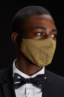 Close up portrait of elegant african-american man wearing face mask while posing against black background at party