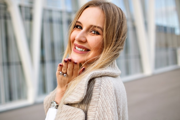 Close up portrait of elegant blonde woman posing on the street wearing coat , natural make up, sensual face and long blonde hairs, windy autumn weather.