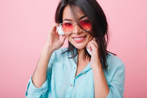 Ritratto del primo piano del modello femminile ispanico elegante indossa occhiali da sole colorati e camicia di cotone. ispirata donna latina in abiti blu che si gode una buona canzone.