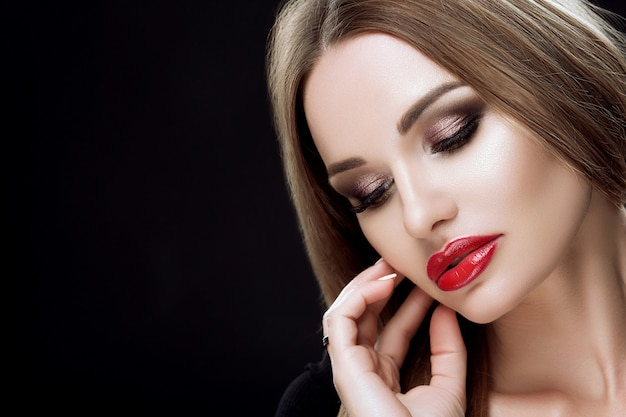 Close-up portrait of an elegant woman with bright makeup, red lips,long lashes, straight long hair, perfect eyebrows, manicure.