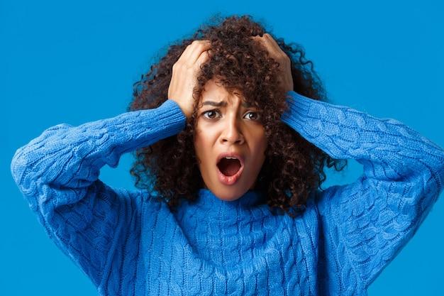 Ritratto del primo piano imbarazzato e scioccato, la giovane donna in preda al panico ha commesso un errore enorme e se ne è pentito, fissando allarmata e nervosa, in piedi vicino al muro blu.
