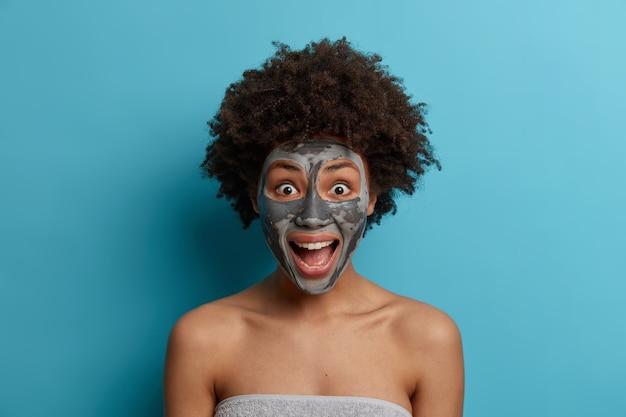 Chiuda sul ritratto della donna dalla pelle scura eccitata emotiva con l'acconciatura afro esclama positivamente, si rilassa con la maschera cosmetica sul viso, essendo in ritardo per la data, sta avvolto in un asciugamano. spa, assistenza sanitaria