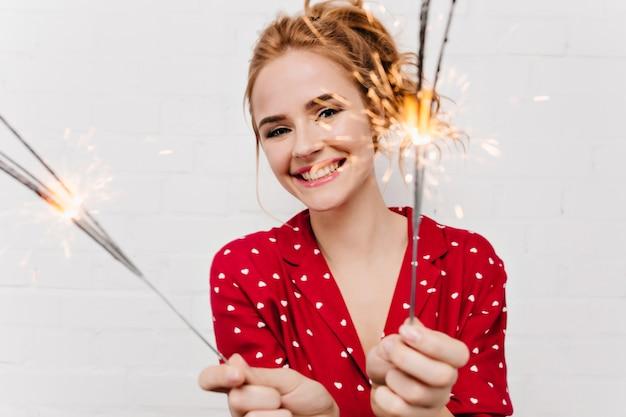 Ritratto del primo piano del modello femminile emotivo che tiene le stelle filanti sulla parete bianca ragazza bionda di risata in camicia rossa che posa con le luci del bengala.