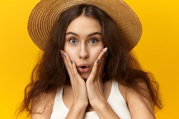 Chiuda sul ritratto della giovane femmina europea divertente emotiva in canotta e cappello di paglia rotondo