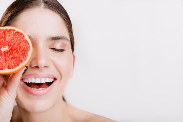 Ritratto del primo piano della ragazza che ride energica senza trucco che copre il viso con arancia siciliana.