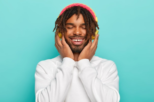 Close up portrait of enthusiastic carefree male model keeps hands on headphones, enjoys cool song, smiles broadly, has dreads, dressed in white sweater and pink hat, being glad and relaxed