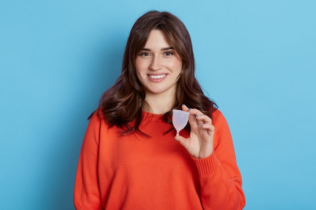 Close up portrait of european woman holding menstrual cup isolated on blue, happy female, having period