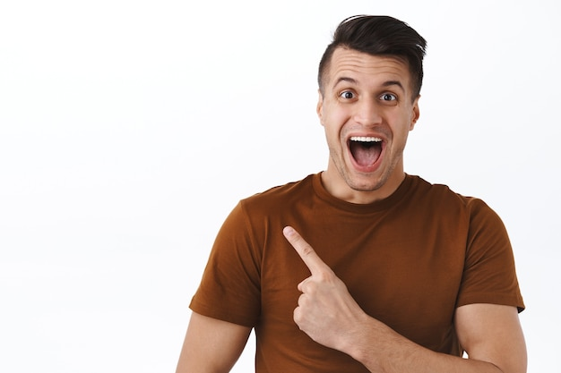 Close-up portrait of excited and amused, happy rejoicing handsome man pointing at upper left corner, showing people awesome promo offer, special discount, hurry up and click link