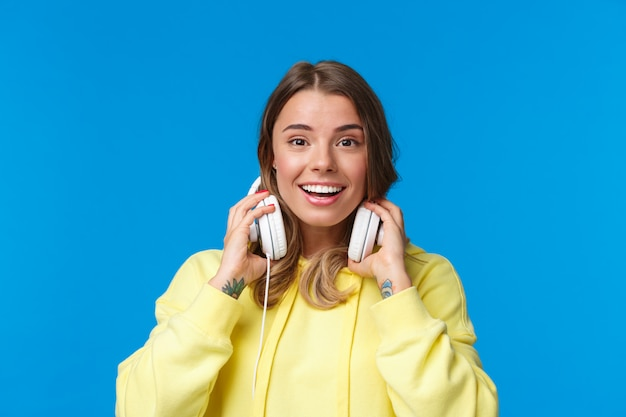 Close-up portrait of excited happy smiling blond girl in yellow hoodie, take-off headphones and grinning as meet friend on street stop by for conversation, standing joyful