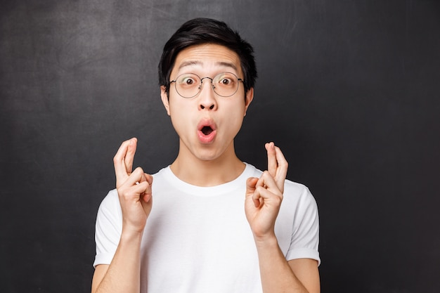 Close-up portrait of excited and hopeful young enthusiastic asian guy in white t-shirt, glasses, cross fingers good luck and staring astounded saying wow, standing black wall amused