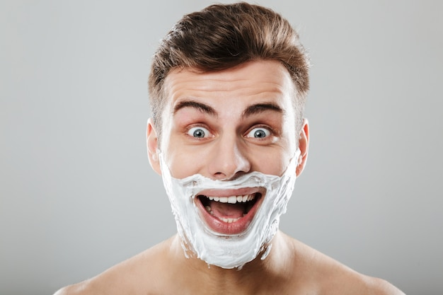 Close up portrait of an excited man with shaving foam
