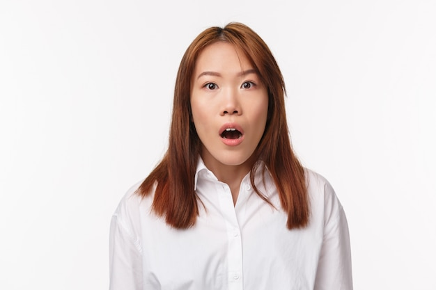 Close-up portrait excited and overwhelmed young asian woman left speechless after hear gossip, stare camera startled gasping drop jaw, looking camera shocked,