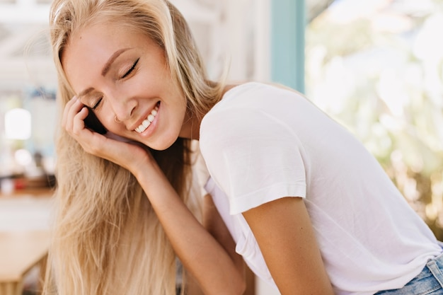 Ritratto del primo piano della donna abbronzata eccitata con capelli lunghi dritti in posa con un sorriso affascinante. foto della ragazza alla moda in maglietta bianca che ride con gli occhi chiusi.