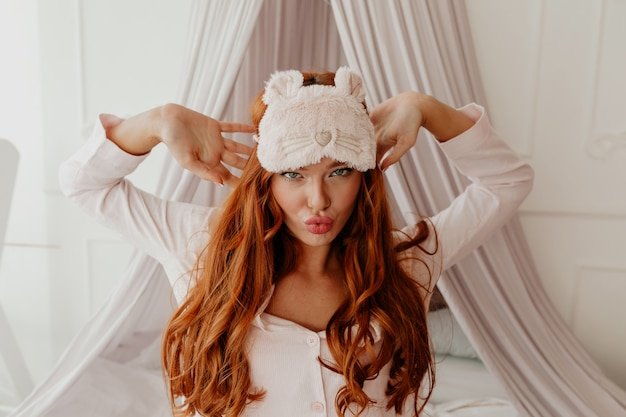Close up portrait of exited funny woman with long wavy red hair with sleeping mask makes faces in the bed