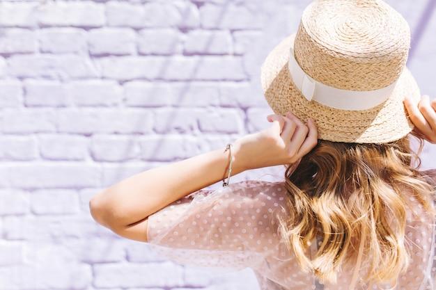 Ritratto del primo piano della ragazza bionda con la pelle leggermente abbronzata in posa con le mani in alto davanti al muro bianco