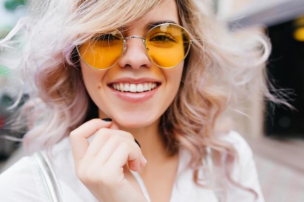 Ritratto del primo piano della ragazza che ride bionda indossa occhiali da sole gialli alla moda