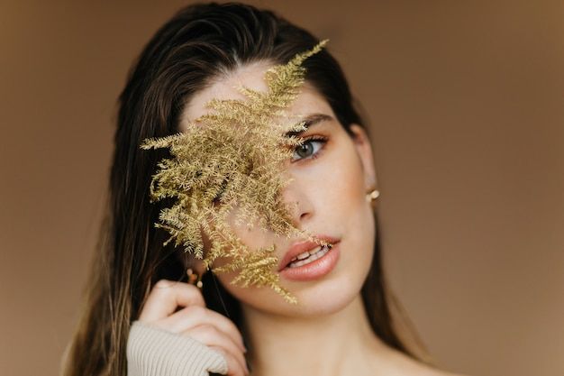 Close-up portrait of fascinating white girl with plant. inspired calm woman standing on brown wall.