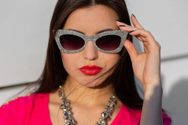 Chiuda sul ritratto della donna castana alla moda in occhiali da sole alla moda e maglietta rosa.