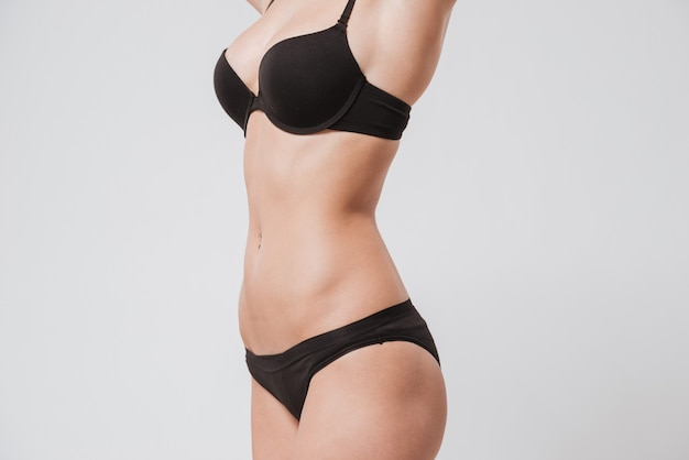 Close up portrait of a female young body wearing black lingerie isolated on white surface