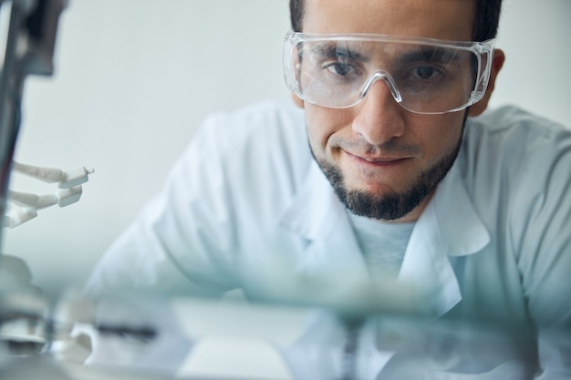 Close up portrait of a focused male engineer in safety goggles monitoring the 3d printing process