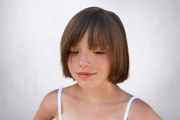 Close up portrait of freckled little child with short stylish hairstyle, looking down while dreaming about something pleasant. beautiful girl with specific appearance posing over white wall