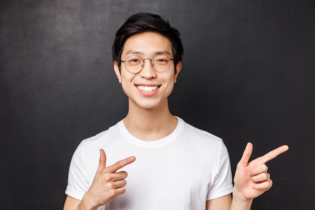 Close-up portrait of friendly smiling asian man in white t-shirt and glasses  confident, pointing fingers right at promo or company banner, give recommendation, black wall