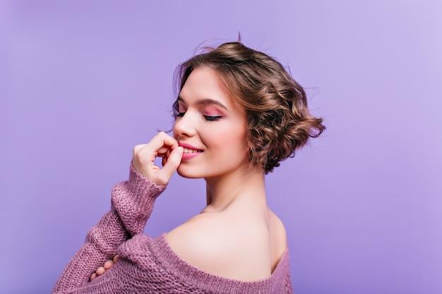 Ritratto del primo piano dal retro del modello femminile bianco estatico che posa sulla parete viola. piacevole ragazza dai capelli corti in abito lavorato a maglia che gode del servizio fotografico