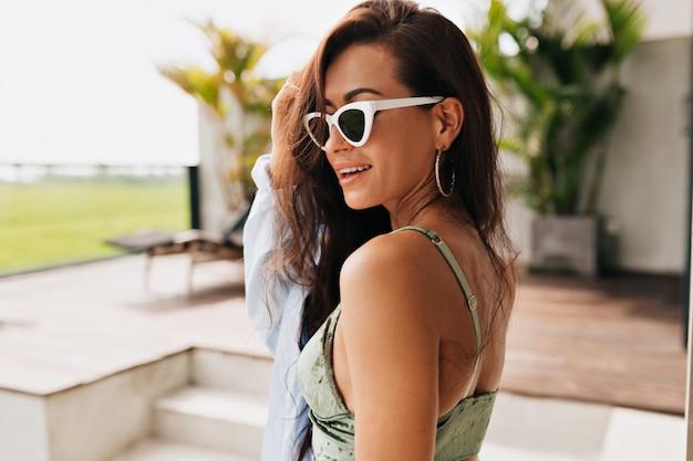여름 안경과 벨벳 탑을 입고 긴 검은 머리를 가진 매력적인 아름다운 여자 뒤에서 초상화를 닫습니다